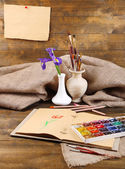 Composition with colorful watercolors, brushes in vase and sketcher on wooden background  — Stok fotoğraf