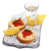 Sandwiches with caviar and vodka on wooden board isolated on white — Stock Photo