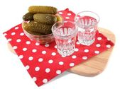 Glasses of vodka and salted cucumbers on wooden board isolated on white — Stock Photo