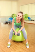 Young woman with gymnastic ball in gym — Stock Photo