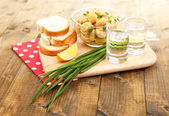 Composition with glasses of vodka and marinated  mushrooms on wooden background — Stockfoto