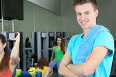 Young trainer in simulator in gym — Stock Photo