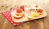 Red caviar in bowl and vodka on wooden board , on napkin on wooden background — Stok fotoğraf