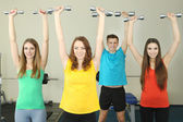 Young beautiful peoples engaged with dumbbells in gym — ストック写真