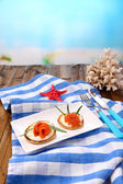 Pancakes with red caviar, salmon and mayo, green onion, on plate, on color napkin, on wooden  table, on bright background — Foto Stock