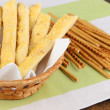 Bread sticks in wicker basket on wooden background — Stock Photo #43447733