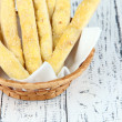 Bread sticks  in wicker basket on wooden background — Stock Photo #43447741