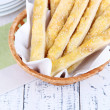 Bread sticks in wicker basket on wooden background — Stock Photo #43447769