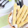 Bread sticks in wicker basket on wooden background — Stock Photo #43447775