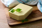 Tasty butter on wooden cutting board  — Stock Photo