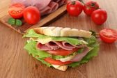 Tasty sandwich with ham on wooden table — Stock Photo