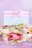 Tasty candies with card on table on bright background — Stockfoto