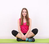 Young beautiful fitness girl exercising on green mat, in gym — Stock Photo