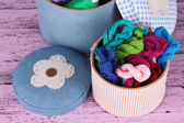 Decorative boxes with colorful skeins of thread on wooden background — ストック写真