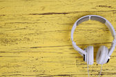 White headphones on wooden table close-up — Stock Photo