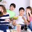 Group of young friends watching television at home — Stock Photo