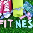 Fitness and healthy life. Conceptual photo. Gumshoes, towel, dumbbells and water bottle on green grass background — Stock Photo #43455785