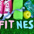 Fitness and healthy life. Conceptual photo. Gumshoes, towel, dumbbells and water bottle on green grass background — Stock Photo #43455819