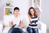 Girl and boy playing video games at home — Stock Photo