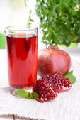 Ripe pomegranates with juice on table on light background — Stockfoto