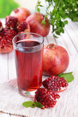 Ripe pomegranates with juice on table on light background — Stock Photo