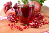 Ripe pomegranates with juice on table close-up — Stockfoto