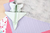 Origami airplane and color papers on wooden table — Stock Photo