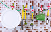 Tableware dried on rope on tile mosaic background — Stock Photo
