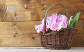 Beautiful tulips in wicker basket, on wooden background — Stock Photo