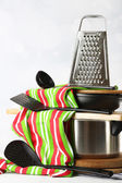 Stacked cooking equipment on wooden table, on light background — Stockfoto