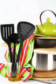 Stacked cooking equipment on wooden table, on light background — Foto Stock