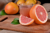 Ripe grapefruit with juice on table close-up — Stock Photo