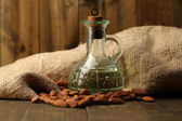 Bottle with almonds oil on color wooden background — Stock Photo