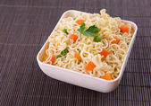 Tasty instant noodles with vegetables in bowl on table close-up — Stock Photo