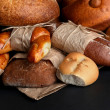 Different types of bread on black background, close-up — Stock Photo