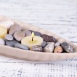 Spa stones and candle in decorative bowl, on color wooden background — Stock Photo #43588969