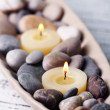 Spa stones and candle in decorative bowl, on color wooden background — Stock Photo #43588977