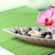 Spa stones and candle in decorative bowl, on wicker mat, on color wooden background — Stock Photo #43588993