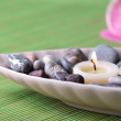 Spa stones and candle in decorative bowl, on wicker mat, on color wooden background — Stock Photo #43588997