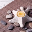 Composition with spa stones, candles on bamboo mat background — Stock Photo #43589037