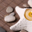 Composition with spa stones, candles on bamboo mat background — Stock Photo #43589039
