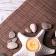 Composition with spa stones, candles on bamboo mat background — Stock Photo #43589047