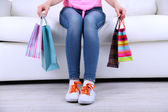 Woman sit on sofa with bags of shopping close-up — Stock Photo