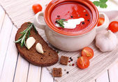 Tasty tomato soup and vegetables on wooden table — Stockfoto