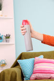 Sprayed air freshener in hand on home interior background — Stock Photo