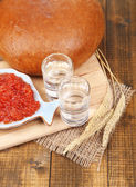 Composition with glasses of vodka  bread and red caviar on wooden table background — Stock Photo