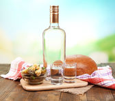 Composition with bottle of vodka and marinated vegetables on wooden table, on bright background — Stock Photo