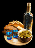Composition with bottle of vodka, glasses, and marinated vegetables on wooden board, isolated on black — Photo