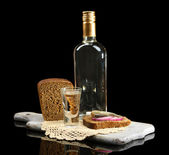 Bottle of vodka, sandwich with salted fish and glasses on wooden board, isolated on black — Stock Photo