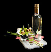Composition with bottle of vodka, snacks with salted fish, green onion and glass on wooden board, isolated on black — Stock Photo